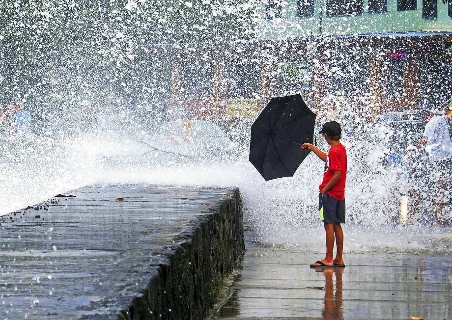 A boy holds an umbrella to a wave in Kailua-Kona on the island of Hawaii, Friday, Aug. 8, 2014. Iselle, the first tropical storm to hit the state in 22 years, knocked out power, caused flooding and downed trees when it crossed onto the Big Island in a rural and sparsely populated region. (AP Photo/Chris Stewart) Photo: Chris Stewart, Associated Press