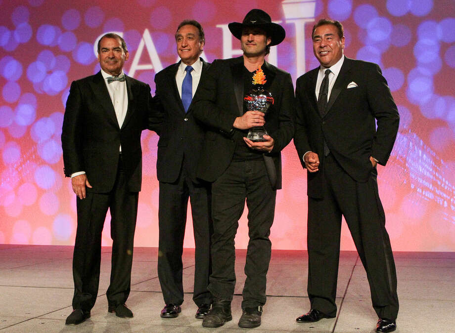 Filmmaker Robert Rodriguez, holding his award, is accompanied by ABC television journalist Jim Avila (from left), Henry Cisneros and ABC News journalist John Quiñones at the gala. Photo: Photos By Marvin Pfeiffer / San Antonio Express-News / Express-News 2014