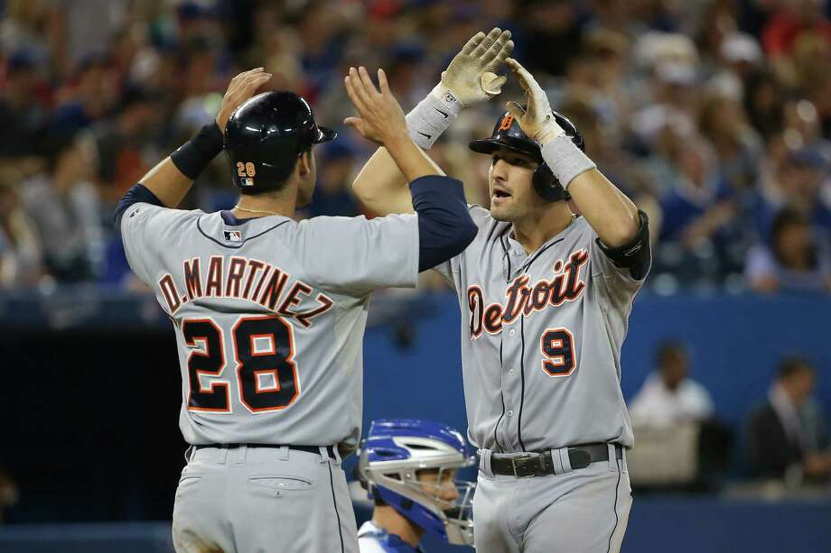 TORONTO, CANADA - AUGUST 8: Nick Castellanos #9 of the Detroit Tigers is congratulated by J.D. Martinez #28 after hitting a two-run home run in the ninth inning during MLB game action against the Toronto Blue Jays on August 8, 2014 at Rogers Centre in Toronto, Ontario, Canada. (Photo by Tom Szczerbowski/Getty Images) ORG XMIT: 477587651 Photo: Tom Szczerbowski / 2014 Getty Images