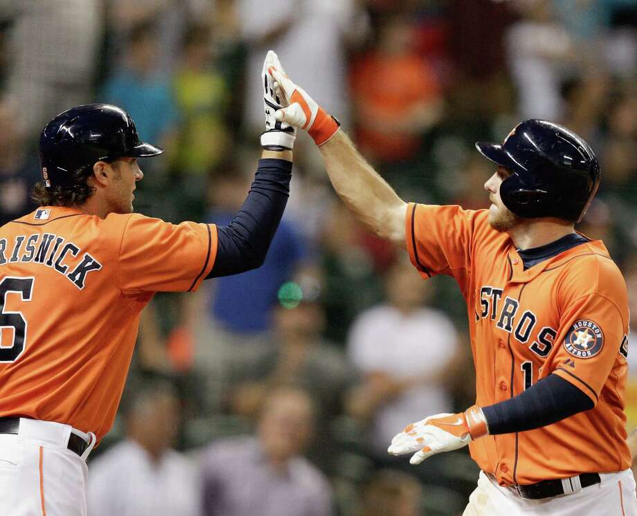 Robbie Grossman, right, warrants a high-five from teammate Jake Marisnick after his eighth-inning homer gave the Astros new life against the Rangers. Photo: Bob Levey, Stringer / 2014 Getty Images
