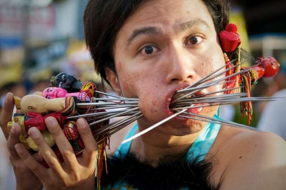 People pierce their cheeks with knives, skewers and other household items. It is believed that the Chinese gods will protect participants from harm or developing scars. Photo: Joseph Ferris III, Wikimedia