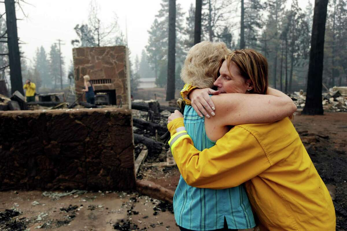 Jenni Garner, right, embraces friend Lynn Westlund at the Fireside Village, a business owned by the Garner Family which was destroyed by the Eiler Fire on Tuesday, Aug. 5, 2014, in Hat Creek, Calif. Thunderstorms that brought light rain and increased humidity to Northern California helped crews make progress Tuesday against two large wildfires that threatened hundreds of homes but also raised the possibility of new lightning-sparked blazes in the region.