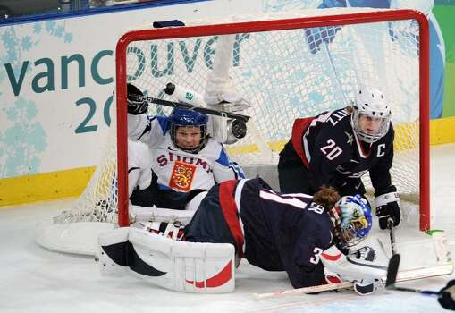 VANCOUVER, BC - FEBRUARY 18:  Anne Helin of Finland falls into the goal next to Natalie Darwitz of the United States and Jessie Vetter of the United States during the ice hockey women's preliminary game between USA and Finland on day 7 of the 2010 Vancouver Winter Olympics at UBC Thunderbird Arena on February 18, 2010 in Vancouver, Canada.  (Photo by Harry How/Getty Images) *** Local Caption *** Jessie Vetter;Anne Heli;Natalie Darwitz Photo: Harry How, Getty Images / 2010 Getty Images
