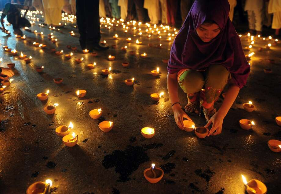A supporter of cleric Tahir-ul-Qadri lights a candle in Karachi, Pakistan, to remember violence victims. Photo: Asif Hassan, AFP/Getty Images