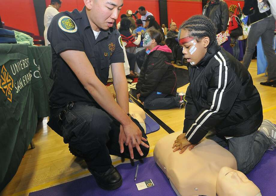 King Zere Bray (right) works with a CPR demonstrator as part of the back-to-school event at the Ella Hill Hutch center. Photo: Josh Edelson