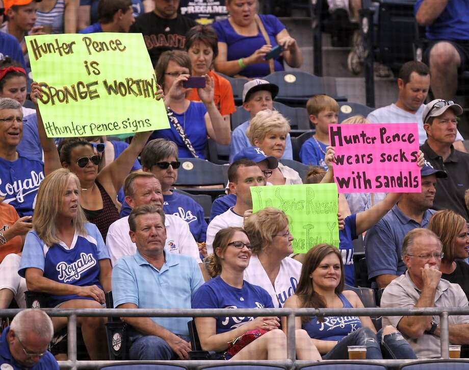 "A clever fan works another ""Seinfeld"" reference (left) into the ""Hunter Pence signs"" movement as the Giants outfielder bats in the first inning of Friday's game in Kansas City. Photo: Ed Zurga, Associated Press"