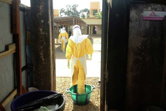 A Doctors Without Borders staffer enters an area where patients confirmed or suspected of having Ebola were being treated in southeastern Guinea earlier this year. Thousands more health workers are needed, experts say.