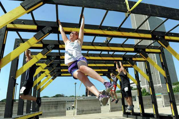 Participants swing across the monkey bars set up on a parking garage rooftop during the Urban RAID race on Saturday, Aug. 9, 2014, in Albany, N.Y. The 5K obstacle course challenged runners with 13 obstacles, including a two-story-high cargo climb, Marine hurdles, ropes and the signature RAID-series wall. (Cindy Schultz / Times Union) Photo: Cindy Schultz / 00028102A