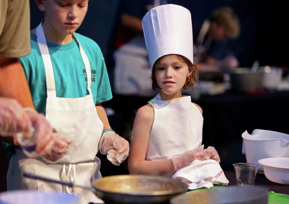 Brayden Hardwick, 10, and sister Brianna, 7, help their dad Kyle, prepare a rice and bean lettuce wrap at the Mars Food Face-Off at Space City Houston Saturday, Aug. 9, 2014, in Houston, Texas. Contestants, assisted by professional chefs, used authentic ingredients viable for a Mars mission, judged on creativity, presentation, nutritional value and taste. Photo: Gary Coronado, Houston Chronicle / © 2014 Houston Chronicle
