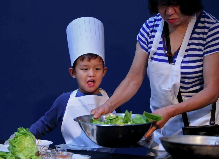 Zane Choi Rigsby, five, with Fen Choi, prepare a Summer Salad at the Mars Food Face-Off at Space City Houston Saturday, Aug. 9, 2014, in Houston, Texas. Contestants, assisted by professional chefs, used authentic ingredients viable for a Mars mission, judged on creativity, presentation, nutritional value and taste. Photo: Gary Coronado, Houston Chronicle / © 2014 Houston Chronicle