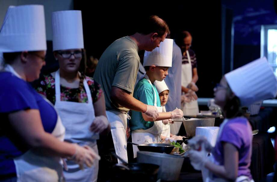 Brayden Hardwick, 10, center, and sister Brianna, 7, help their dad Kyle, prepare a rice and bean lettuce wrap at the Mars Food Face-Off at Space City Houston Saturday, Aug. 9, 2014, in Houston, Texas. Contestants, assisted by professional chefs, used authentic ingredients viable for a Mars mission, judged on creativity, presentation, nutritional value and taste. Photo: Gary Coronado, Houston Chronicle / © 2014 Houston Chronicle