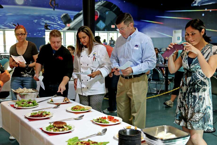 Former Space Shuttle Commander Ken Cameron, fourth from the left, surveys the plates with other judges at the Mars Food Face-Off at Space City Houston Saturday, Aug. 9, 2014, in Houston, Texas. Contestants, assisted by professional chefs, used authentic ingredients viable for a Mars mission, judged on creativity, presentation, nutritional value and taste. Cameron was aboard three Shuttle missions. Photo: Gary Coronado, Houston Chronicle / © 2014 Houston Chronicle