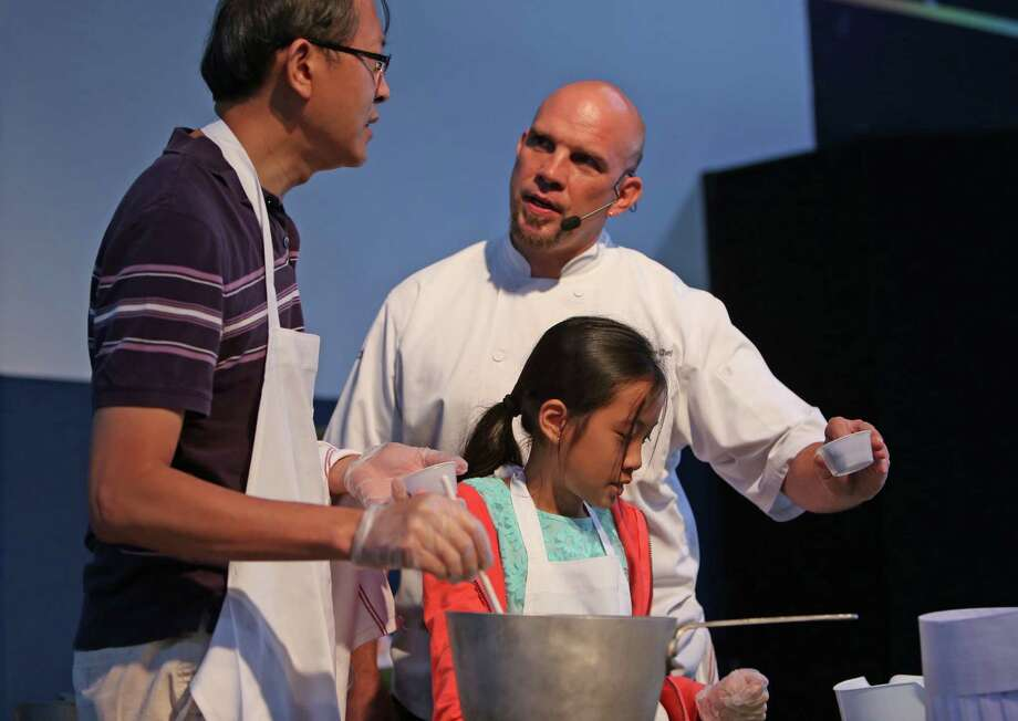 David Lin, left, with daughter Kaydence Lin, 10, with celebrity chef Shane Miller, preparing the Universe Breakfast Plate, at the Mars Food Face-Off at Space City Houston Saturday, Aug. 9, 2014, in Houston, Texas. Contestants, assisted by professional chefs, used authentic ingredients viable for a Mars mission, judged on creativity, presentation, nutritional value and taste. Photo: Gary Coronado, Houston Chronicle / © 2014 Houston Chronicle