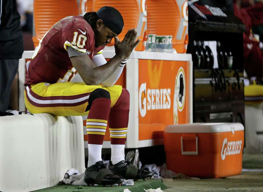ADVANCE FOR WEEKEND EDITIONS, AUG. 9-10 -  FILE - In this Jan. 6, 2013 file photo, Washington Redskins quarterback Robert Griffin III sits on the bench after being injured during an NFL wild card playoff football game against the Seattle Seahawks in Landover, Md. Broken bones. Torn ligaments. Subpar performances. They all combined to sideline some of the NFL's biggest stars a year ago, a lost season for several players who'd rather make headlines on the field instead of the trainers' room. (AP Photo/Evan Vucci, File) Photo: Evan Vucci, Associated Press / AP