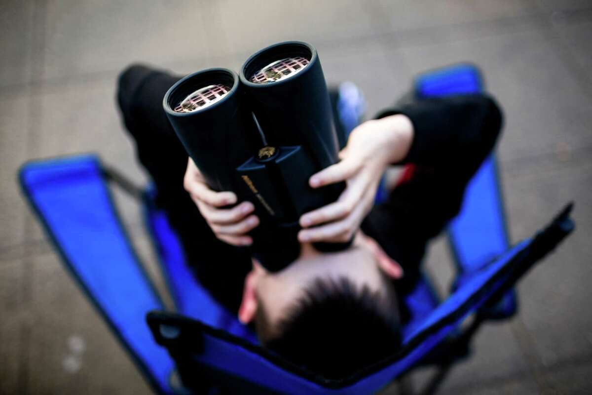 A young boy peers through binoculars at brave individuals rappelling down the 40 stories,