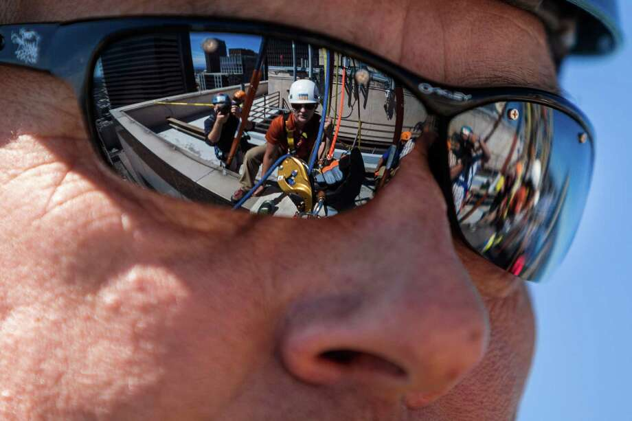 Seattle skyline and rope riggers are reflected in the glasses of Major Bambino before he descended the 40 stories. Photo: JORDAN STEAD, SEATTLEPI.COM / SEATTLEPI.COM