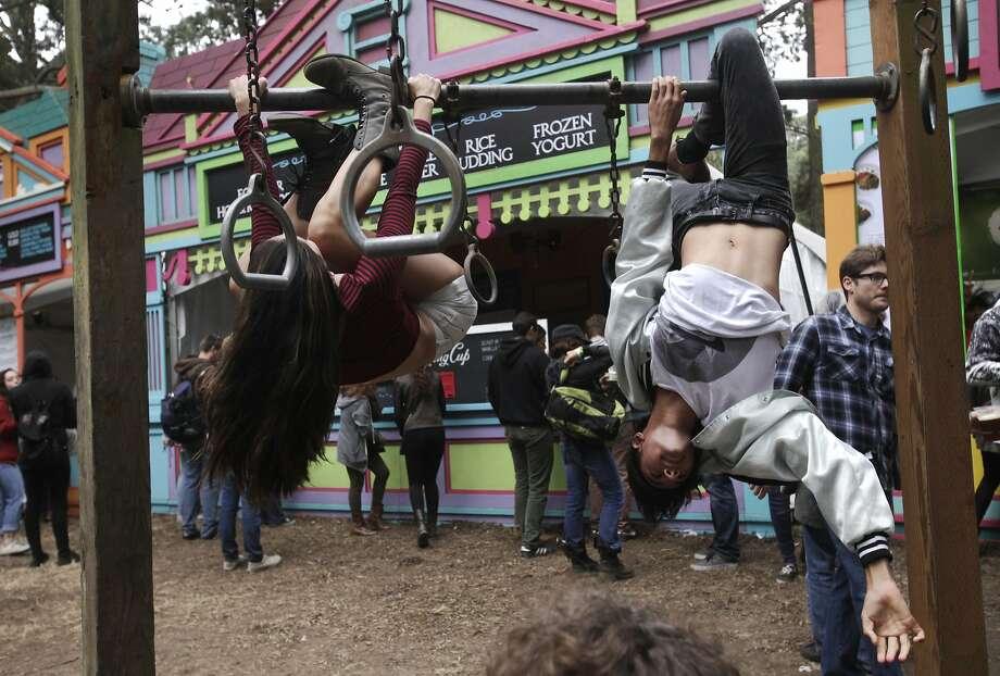 Siblings Lena, 19, left, and Javan Tahir, 16, hang upside-down during Outside Lands music festival August 9, 2014 in Golden Gate Park in San Francisco, Calif. Photo: Leah Millis, The Chronicle