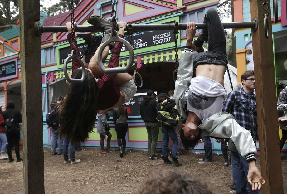 Siblings Lena, 19, left, and Javan Tahir, 16, hang upside-down during Outside Lands music festival August 9, 2014 in Golden Gate Park in San Francisco, Calif. Photo: Leah Millis, The Chronicle