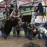 Siblings Lena, 19, left, and Javan Tahir, 16, hang upside-down during Outside Lands music festival August 9, 2014 in Golden Gate Park in San Francisco, Calif.