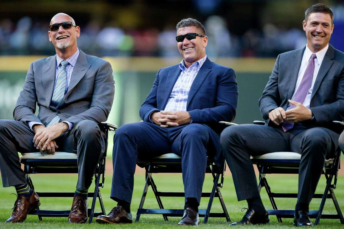 From left, Jay Buhner, Edgar Martinez, and Dan Wilson, all Mariners Hall of Fame members, laugh during a ceremony for Lou Piniella.