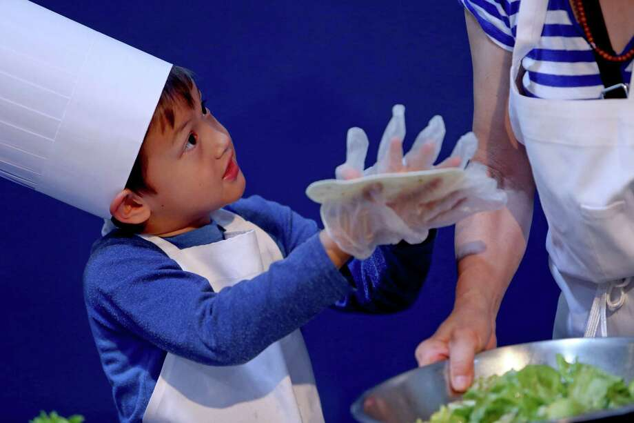 Zane Choi Rigsby, 5, had 30 minutes - and help from Fen Choi - to prepare a Summer Salad for the Mars Food Face-Off at Space City Houston on Saturday, using authentic ingredients viable for a Mars mission, judged on creativity, presentation, nutrition and taste. Photo: Gary Coronado, Staff / © 2014 Houston Chronicle