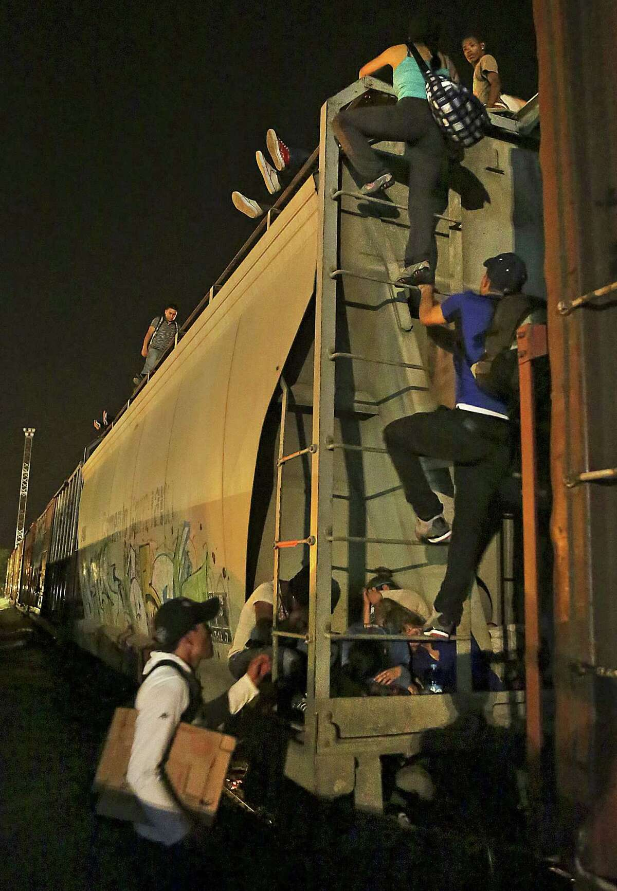 Migrants seeking a better life in the U.S. board the train known as La Bestia, The Beast, in Arriaga, Mexico.