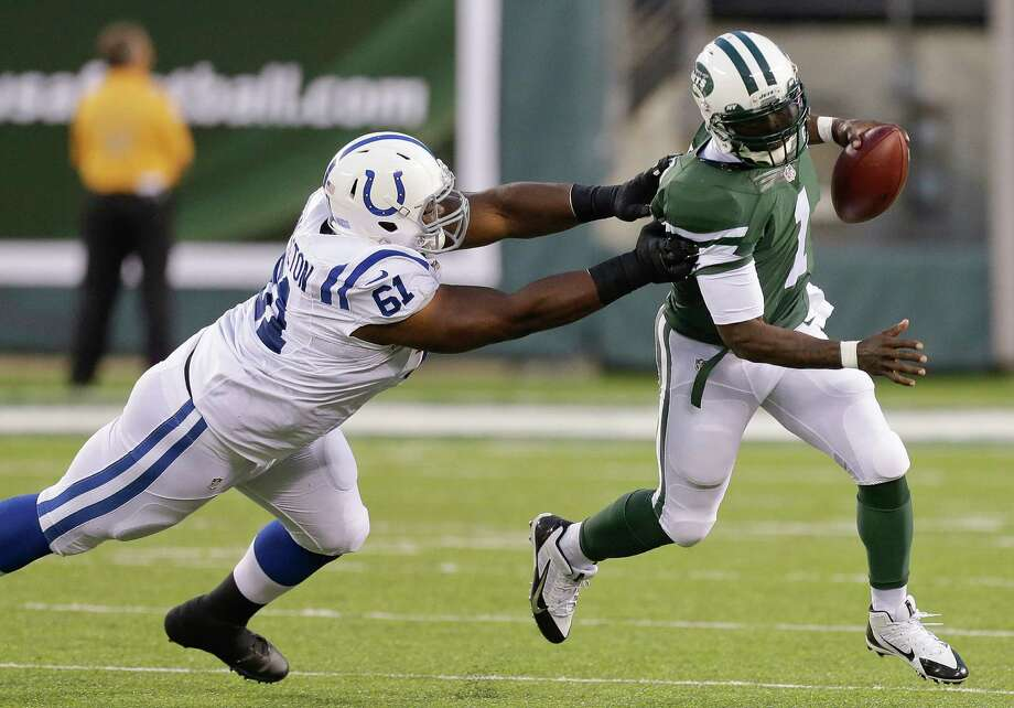 New York Jets quarterback Michael Vick (1) avoids Indianapolis Colts defensive tackle Jeris Pendleton (61) in the second quarter of a preseason NFL football game, Thursday, Aug. 7, 2014, in East Rutherford, N.J. (AP Photo/Frank Franklin II)  ORG XMIT: ERU115 Photo: Frank Franklin II / AP
