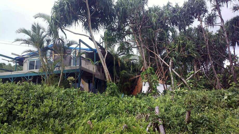 Tropical Storm Iselle battered this home as it blew through Puna, Hawaii, where it damaged roofs, toppled trees and knocked out electricity. Photo: Andrew Fujimura, Associated Press