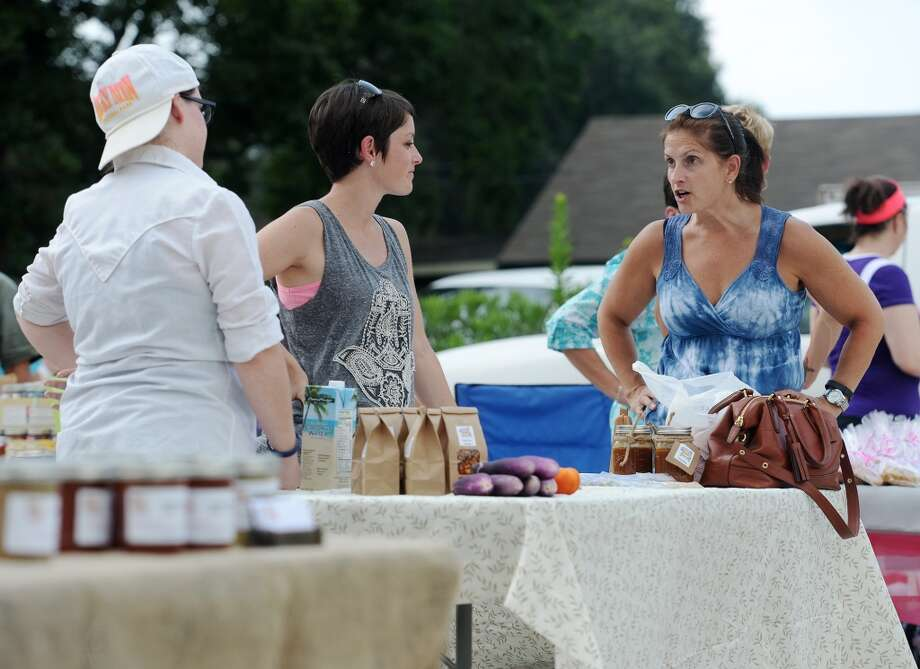 Jodi Hubert, Chrystal Lundy, and Maggie Duplantis, left to right, talk at the Cave-Momma's Quest booth on Tuesday. Down to Earth, a Nederland shop that specializes in locally produced natural and organic items, has launched a Tuesday afternoon farmers market in their parking lot. Photo taken Tuesday 7/22/14 Jake Daniels/@JakeD_in_SETX
