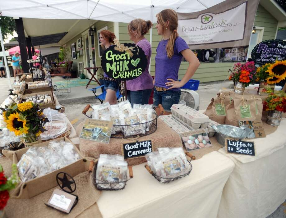Kaitlyn, Shari, and Chloe Cribbs, back to front, man the Beau-tanicals booth at the Down to Earth farmers market Tuesday afternoon. Down to Earth, a Nederland shop that specializes in locally produced natural and organic items, has launched a Tuesday afternoon farmers market in their parking lot. Photo taken Tuesday 7/22/14 Jake Daniels/@JakeD_in_SETX
