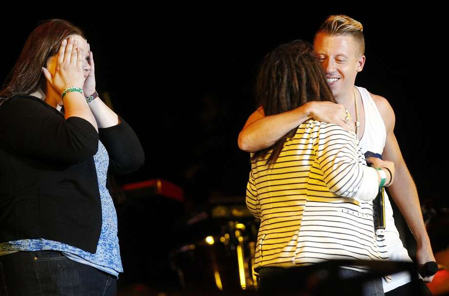 Macklemore hugs two women after one proposed to her partner on stage during his and Ryan Lewis' performance during Outside Lands music festival August 9, 2014 in Golden Gate Park in San Francisco, Calif. Photo: Leah Millis, The Chronicle