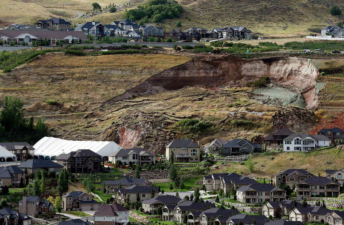 This Tuesday, Aug. 5, 2014 photo shows the area of a landslide in a hillside community of North Salt Lake, Utah. One home has been destroyed and at least a dozen others have been evacuated. (AP Photo/The Deseret News, Ravell Call)