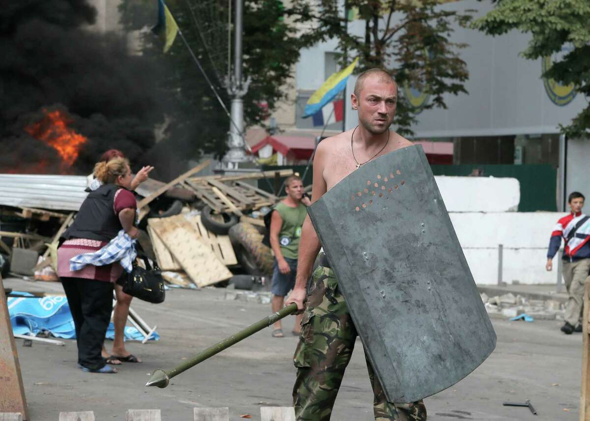 The dweller of the tent camp that has blocked the main street of Ukraine's capital since protests that toppled the government earlier this year, stands guard as volunteers arrive to clear the square in Kiev, Ukraine, Saturday, Aug. 9, 2014. Protesters erected the barricades to protect a sprawling tent camp on the central city's main square. Although the camp's size dwindled sharply after President Viktor Yanukovych fled the country in February and a new government came to power, a determined core of demonstrators remained in a show of suspicion of the new authorities. Some tents remained on Saturday. But Kiev mayor Vitali Klitschko, who was one of the leaders of the protests against Yanukovych, was quoted by Ukrainian media as saying an agreement has been reached with the protest holdouts to restore free movement in the center.