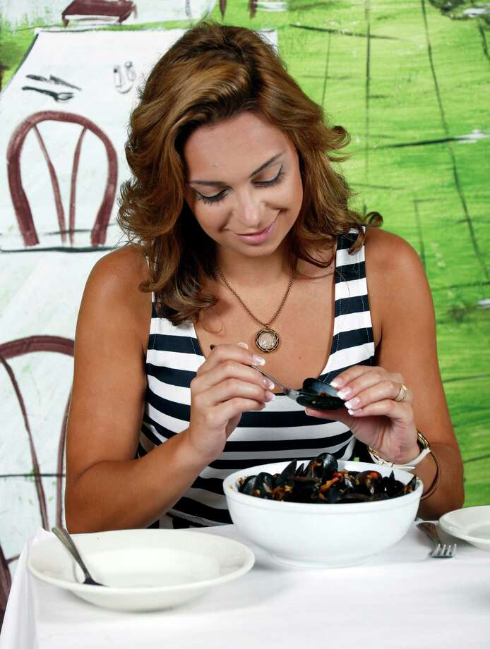 Model Eve Korun demonstrates how to eat mussles at La Frite Belgian  Bistro in Southtown. La Frite owner Miles Donnelly says you should eat the first mussel out of the shell ... Photo: William Luther, San Antonio Express-News / © 2014 San Antonio Express-News