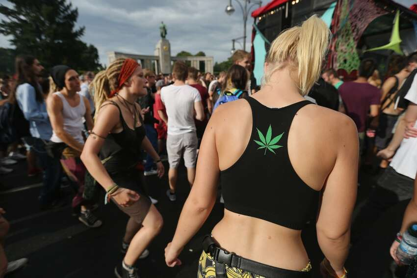 Participants, including one with a marijuana leaf emblem on her back, dance at the annual Hemp Parade (Hanfparade) on August 9, 2014 in Berlin, Germany. Supporters of cannabis legalization are hoping legalized sale in parts of the USA will increase the likelihood of legalization in Germany. The city of Berlin is considering allowing the sale of cannabis in one city district. (Photo by Sean Gallup/Getty Images)