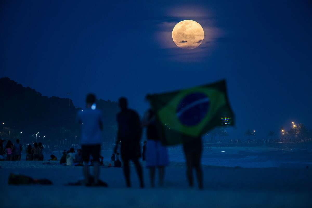 """The full moon, nicknamed """"the supermoon"""", rises at Ipanema beach in Rio de Janeiro, Brazil, on August 10, 2014. A supermoon is the coincidence of a full moon or a new moon with the closest approach the Moon makes to the Earth on its elliptical orbit, resulting in the largest apparent size of the lunar disk as seen from Earth. AFP PHOTO / YASUYOSHsilleterosI CHIBAYASUYOSHI CHIBA/AFP/Getty Images"""