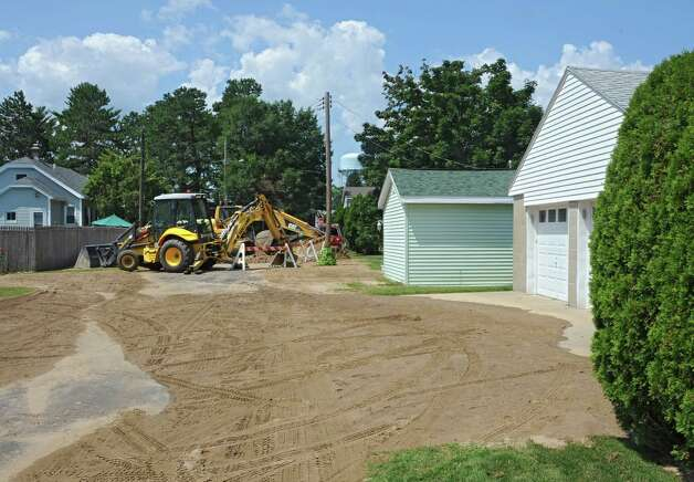Backhoes are seen on Bernard St. at a large hole in the road on Sunday, Aug. 10, 2014 in Rotterdam, N.Y. There was a water main break there a few days earlier and houses had flood damage. (Lori Van Buren / Times Union) Photo: Lori Van Buren / 10028091A