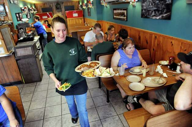 Server Holly McDermott, center, delivers meals to customers on Saturday, Aug. 9, 2014, at Bob's Diner in Watervliet, N.Y. (Cindy Schultz / Times Union) Photo: Cindy Schultz / 00028111A