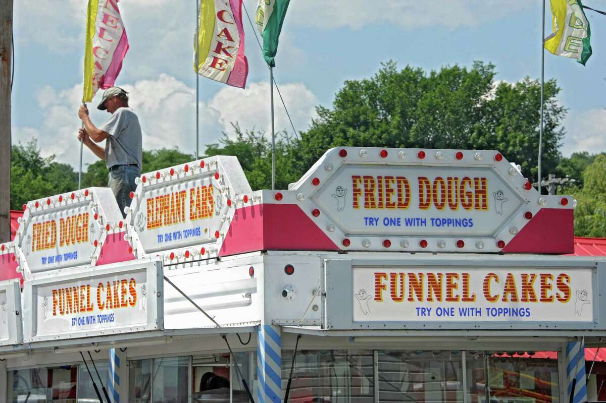 Patrick Wright of Brant, N.Y. sets up the flags on top of the Fried Dough and Funnel Cakes business he works at the Altamont Fair on Sunday, Aug. 10, 2014 in Altamont, N.Y. The fair runs Aug. 12-17. (Lori Van Buren / Times Union)