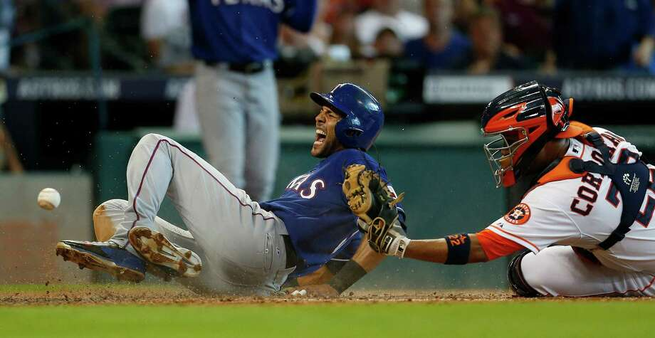 Astros catcher Carlos Corporan, right, fails to make a tag on the Rangers' Alex Rios, who was injured on the play at home plate while scoring to tie the game at 2 during the fourth inning Sunday at Minute Maid Park. Photo: Karen Warren, Staff / © 2014 Houston Chronicle