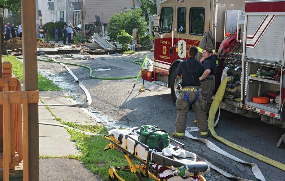 Emergency workers tend to a vacant house that exploded in the Hamilton Hill neighborhood after an apparent gas leak on Sunday, Aug. 10, 2014 in Schenectady, N.Y. It was unknown if anybody was inside. (Lori Van Buren / Times Union) Photo: Lori Van Buren / 10028091A