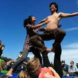 Hannah Yang helps balance Holman Gao as Amanda Bullington holds him up as they practice acro-yoga at Outside Lands Music Festival in Golden Gate Park on August 10, 2014 in San Francisco, CA.