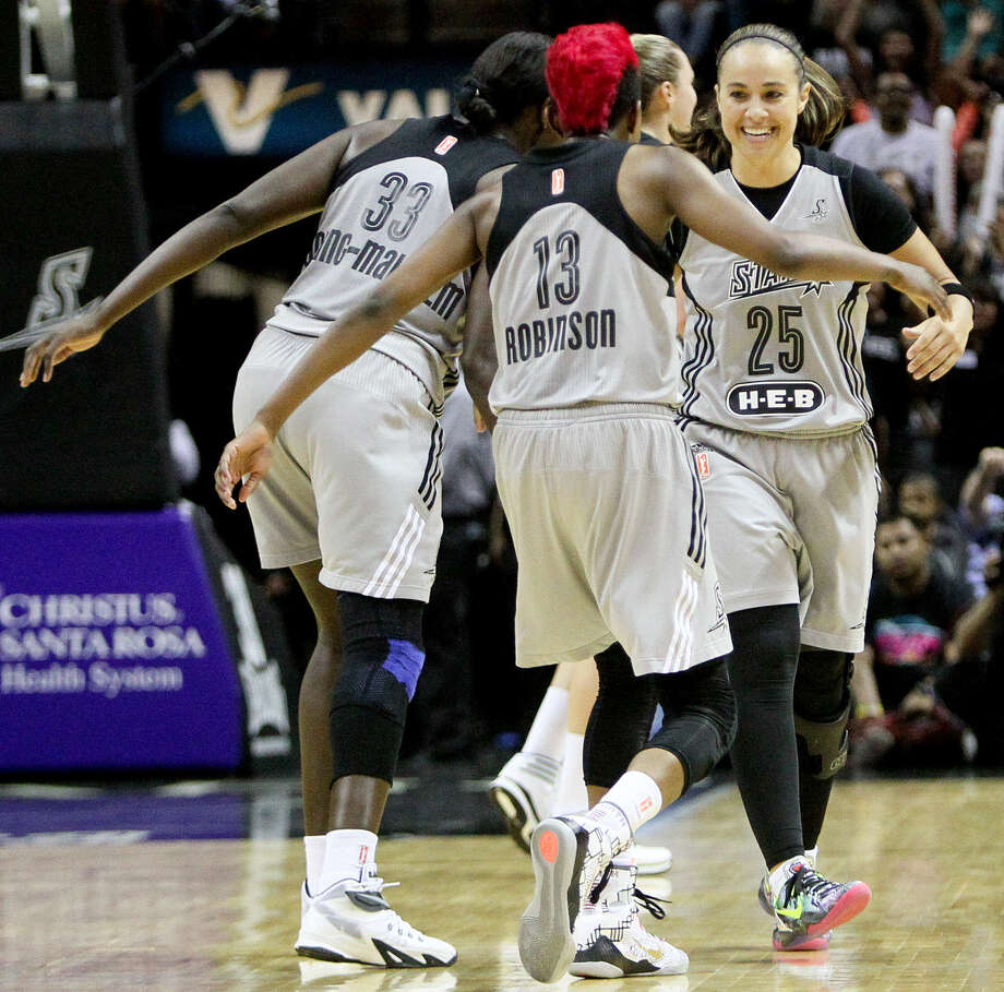 Sophia Young-Malcolm (left) and Danielle Robinson (center) celebrate with Becky Hammon after the guard's 3-pointer with 26.2 seconds left put the Stars ahead 78-74. The Stars can clinch a playoff berth by winning one of their remaining two games. Photo: Marvin Pfeiffer / San Antonio Express-News / Express-News 2014