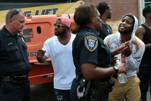 Jamahl Spence, right, pleads his case with a Normandy police officer in front of the Ferguson, Mo. police station on Sunday, Aug. 10, 2014, one day after a Ferguson officer shot and killed Michael Brown. Photo: Robert Cohen, Associated Press