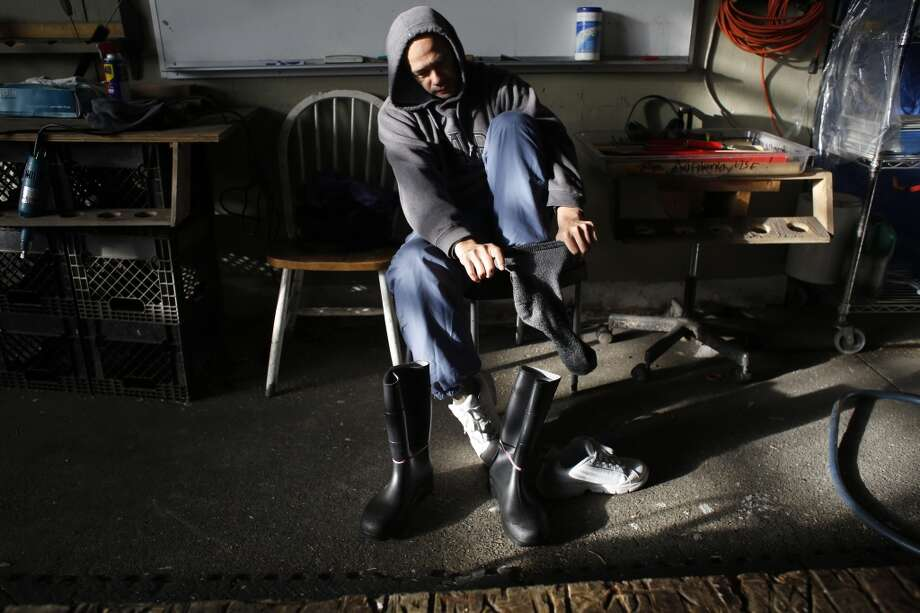 Master ice sculptor Anthony Soriano puts on an extra layer of socks and rubber boots before a morning of ice sculpting at the San Francisco Ice Company in San Francisco, Calif. Photo: Mike Kepka