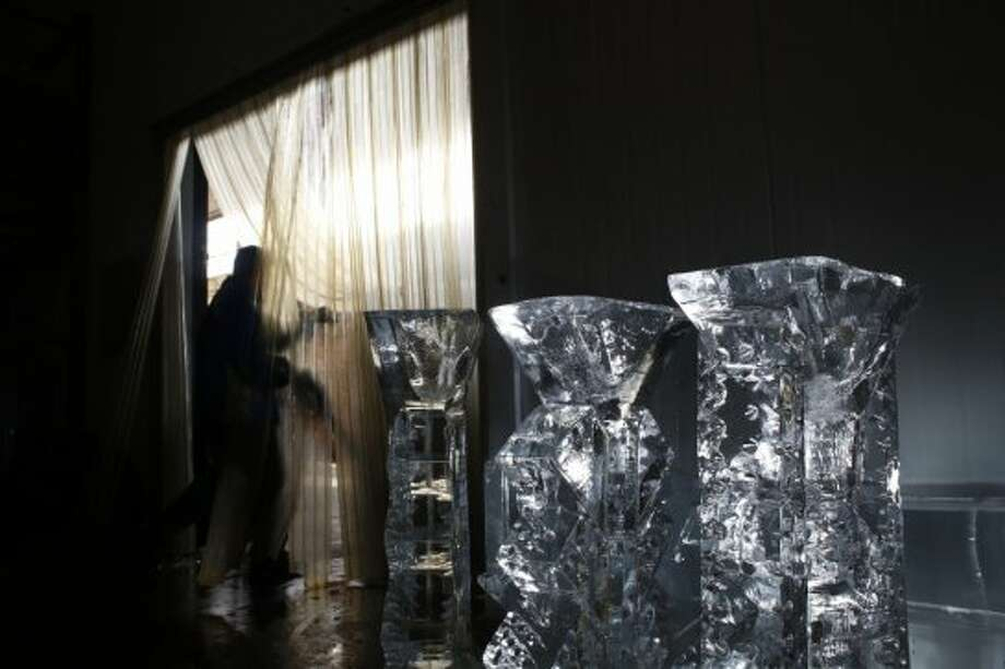 Opening the freezer door, master ice sculptor Anthony Soriano checks on a trio of newly completed ice sculptures at the San Francisco Ice Company in San Francisco, Calif. Photo: Mike Kepka
