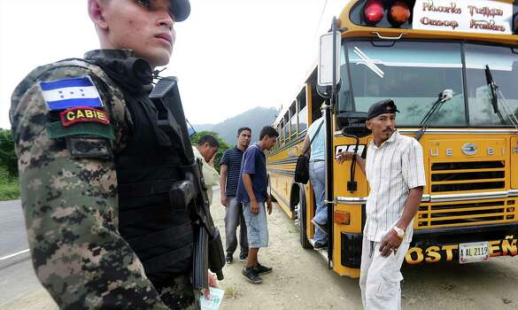 A Military Police officer stands guard as passengers re-board a bus on its' way to Guatemala after being checked for authorized papers near Corinto, Honduras at the Guatemala border. Friday, June 27, 2014. Photo: Bob Owen, San Antonio Express-News / ©2013 San Antonio Express-News