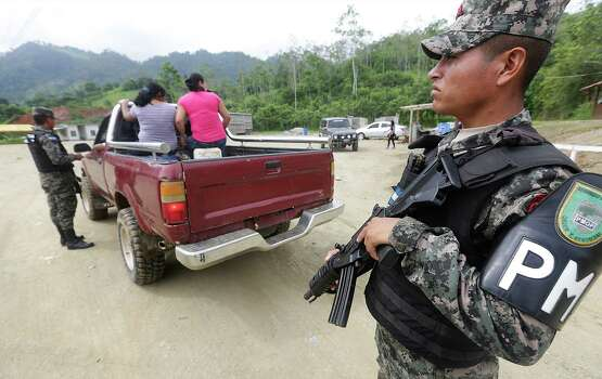 A Honduran Military Police stands guard as a truck is inspected at a military check point near Corinto, Honduras at the Guatemala border. Friday, June 27, 2014. Photo: Bob Owen, San Antonio Express-News / ©2013 San Antonio Express-News