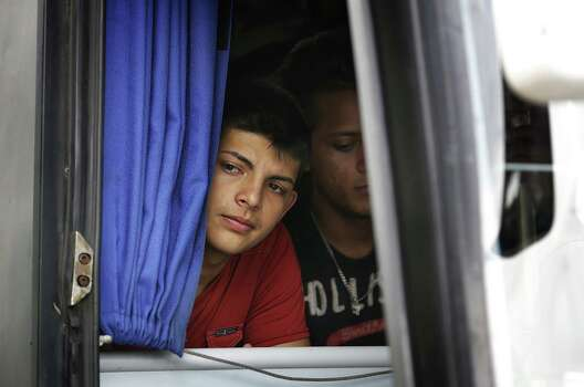 A deported Honduran teenager peers out a Mexican bus as it arrives in Corinto, Honduras, at the Guatemala border. Friday, June 27, 2014. A total of 7 busses returned a total of 254 adults and children that were apprehended in Mexico. Photo: Bob Owen, San Antonio Express-News / ©2013 San Antonio Express-News