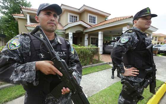 The SWAT team of the Honduras Military Police stand guard in front of one of three luxury homes in the subdivision of El Pedregal in San Pedro Sula.  The homes are owned by area drug and human trafficking groups that are rented out to launder money. Thursday, June 26, 2014. Photo: Bob Owen, San Antonio Express-News / ©2013 San Antonio Express-News
